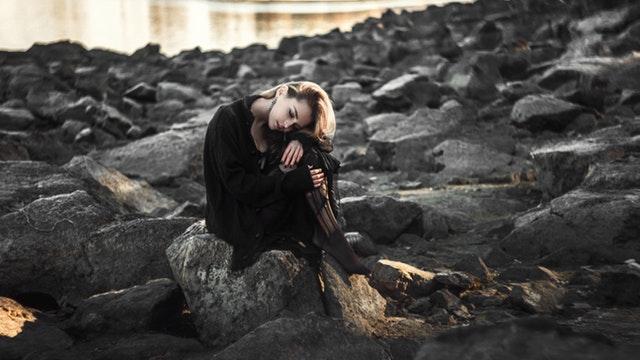 喪服を着て一人悲しんでいる様子の女性の画像