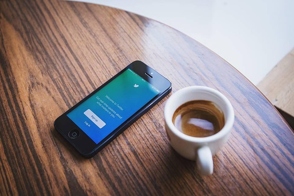 ツイッターにサインインしようとしているスマホと飲みかけのエスプレッソの画像