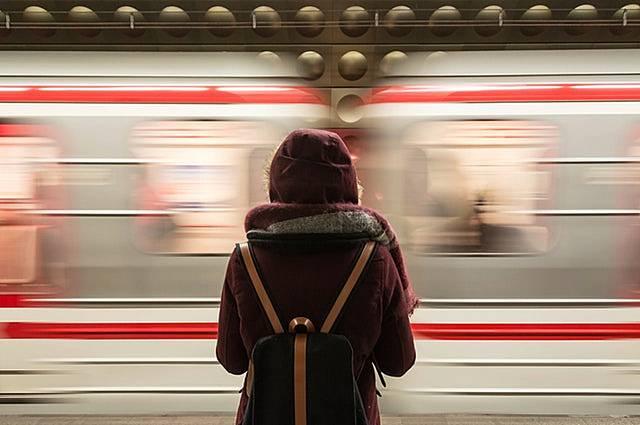 通過電車を見送るバックパッカーの画像