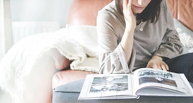 友達が写っているアルバムを面白くなさそうに見ている女性の画像
