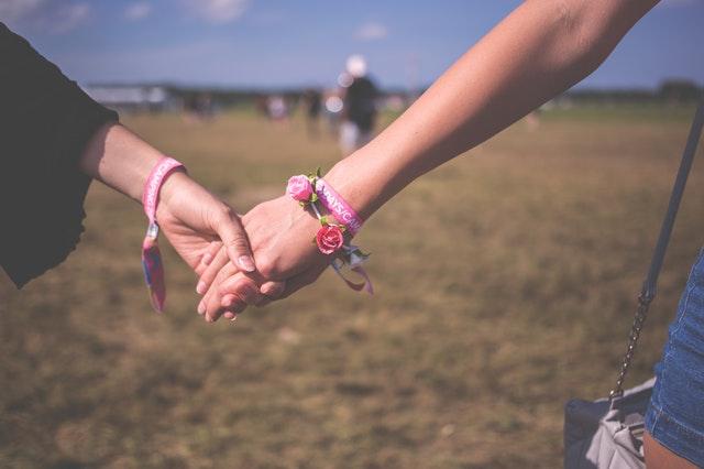 応えられない好意をを持ってくれている人と手を繋いでいる画像