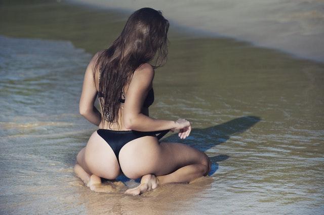 海辺で水着姿の女性が砂浜に座っている画像