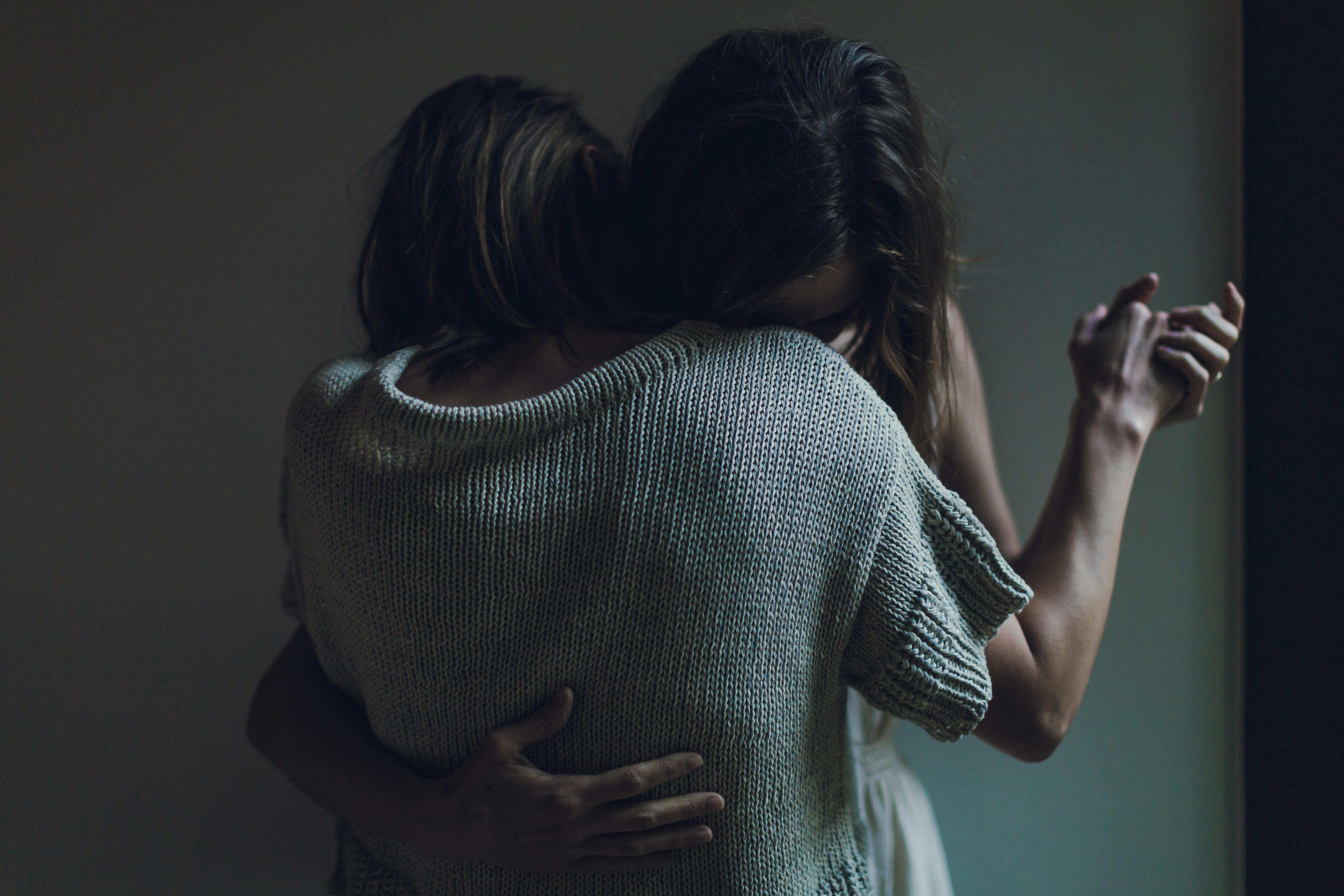 手を握り抱き合ってさよならを言う姉妹の画像