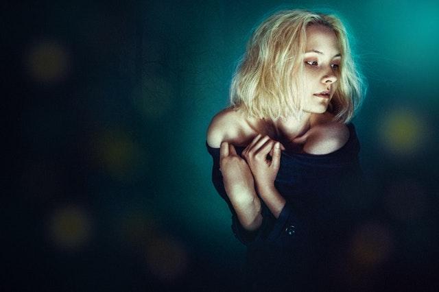 薄暗い闇の中にいる女性の画像
