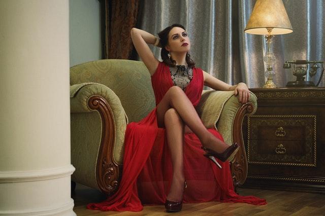 真っ赤なドレスを着た外国人女性が脚を組みながら考えているサムネイル画像