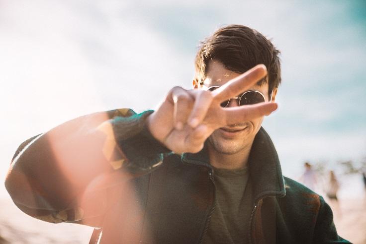 丸いサングラスをかけた男性がピースサインをしながらにやける画像