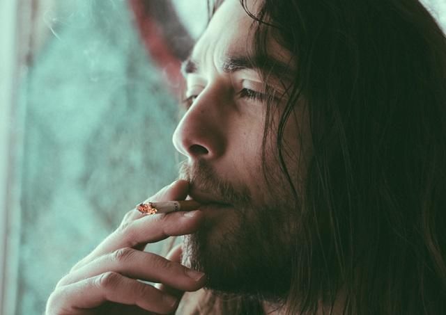 長髪の男性がタバコを吸っている画像