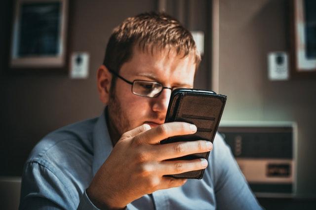 スマートフォンをいじっている小太りな男性の画像
