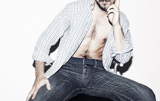 デニムを履いてシャツを羽織っている毛の濃い男性の画像