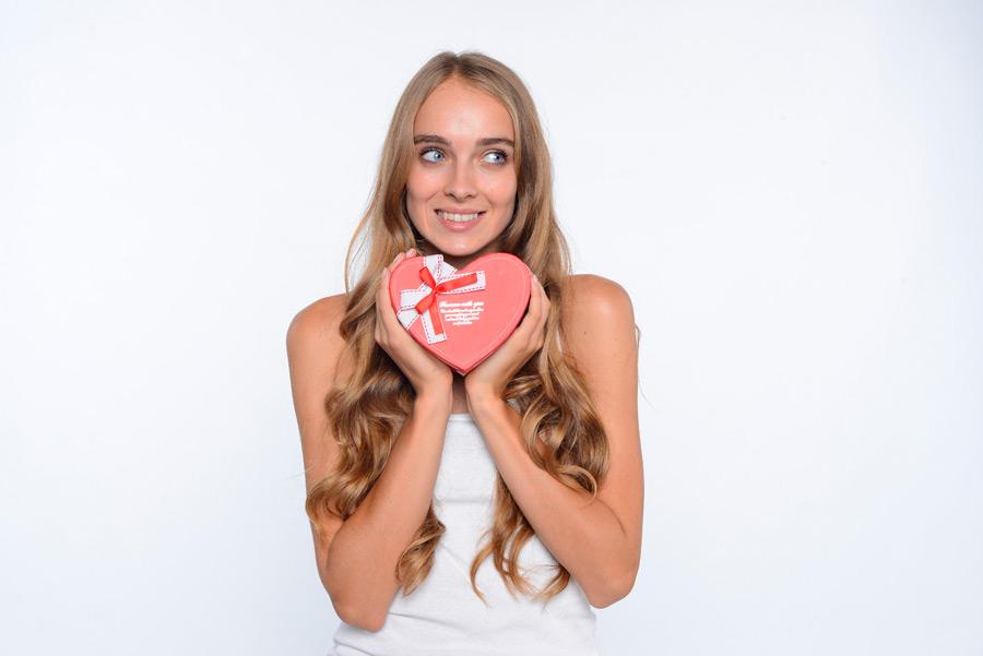 ハート型のバレンタインプレゼントを胸元に持って嬉しげな女性の画像