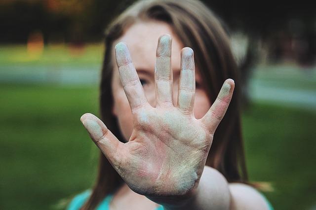 女性が白い手の平をこちらに向けて拒否している画像