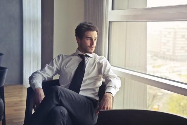 スーツ姿のイケメンが物憂げに窓の外を眺めている画像