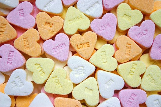 オレンジ、紫、黄色、白のハート型のキャンディが並ぶサムネイル画像
