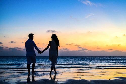 海辺をゆったり歩くカップル