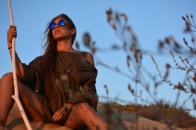 棒を持って荒野に座る女性の画像