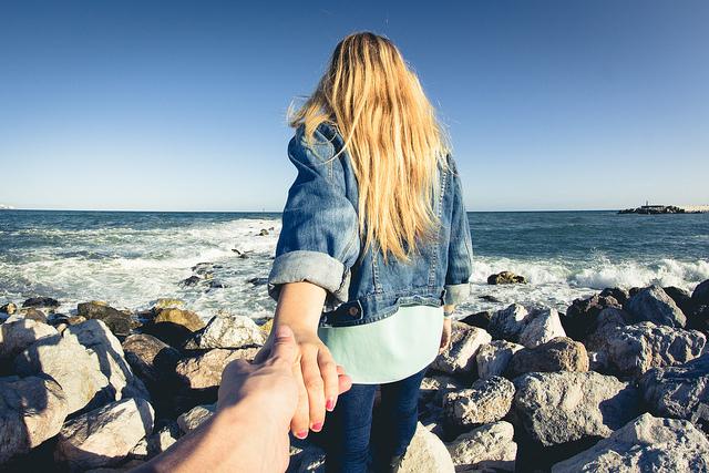 岩の転がる海辺を男性の手を引いて歩く金髪の女性の#followmeto画像