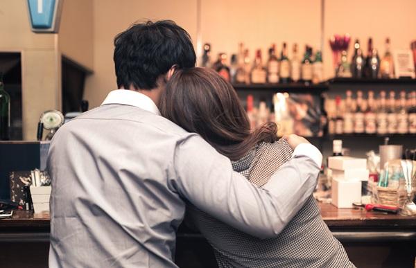 サシ飲みで男性にお持ち帰りされようとバーカウンターでもたれかかっている女性の後ろ姿の画像