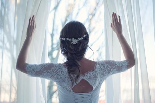 窓を開けるウェディングドレスの女性の画像