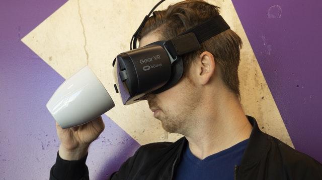 VRゴーグルをつけたままコーヒーを飲もうとする男性の画像