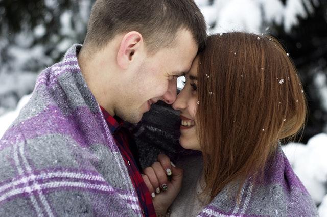 雪が舞い散るなか1つのマフラーを2人で使うカップルの画像