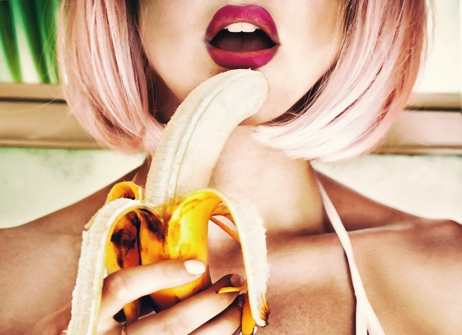 水着姿の女性がバナナを手に持って口にあてがっている画像