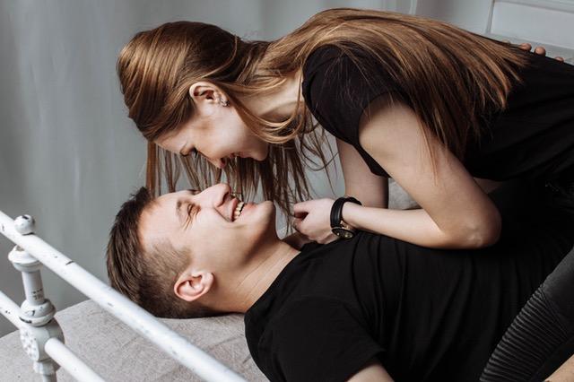 男女がベッドの上で微笑み合う画像