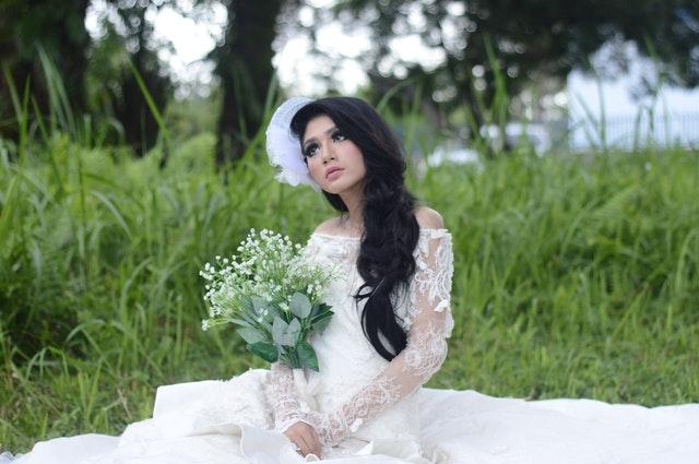 ブーケを持って草原に座り物憂げな表情のウェディングドレス姿の女性の画像