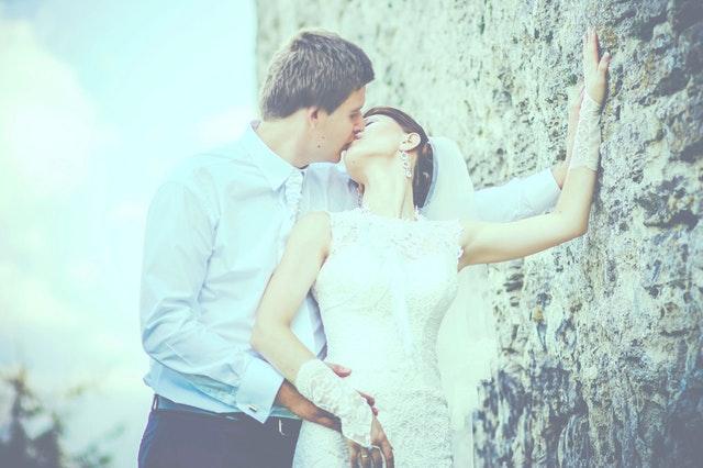 シャツ姿の男性が振り向くノースリーブのウェディングドレス姿の女性とキスしている画像