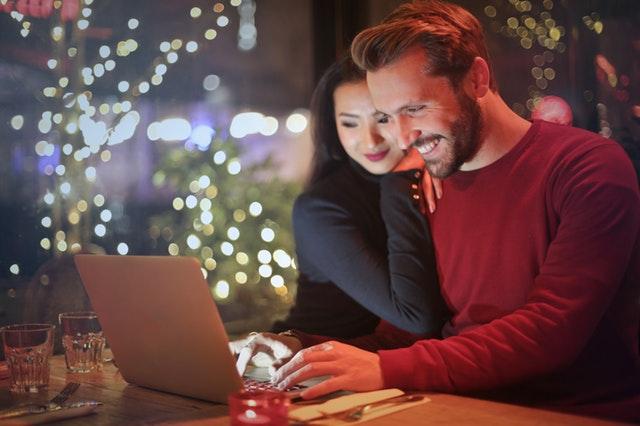 ひとつのパソコンを2人で見つめながら微笑んでいるカップルの画像