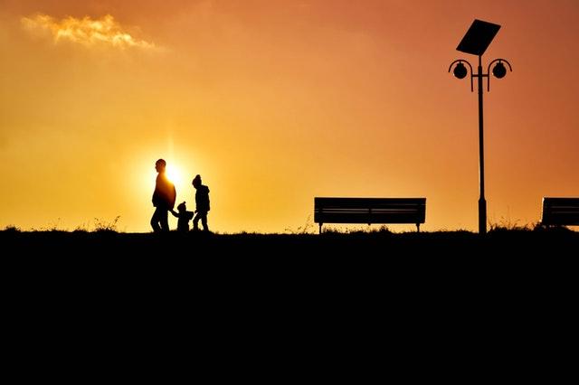 夕焼けに浮かび上がる家族旅行者のシルエット