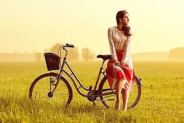 自転車に腰掛けながら黄昏る女性の画像