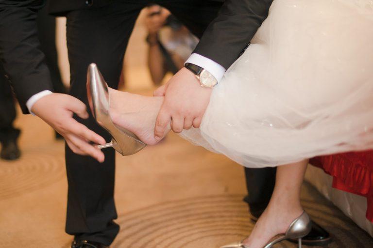 新郎に銀色のヒールを履かせてもらっているウェディングドレス姿の女性の画像