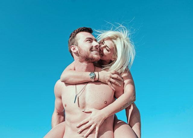 裸の男性に後ろから抱きついて頬にキスする裸の女性の画像