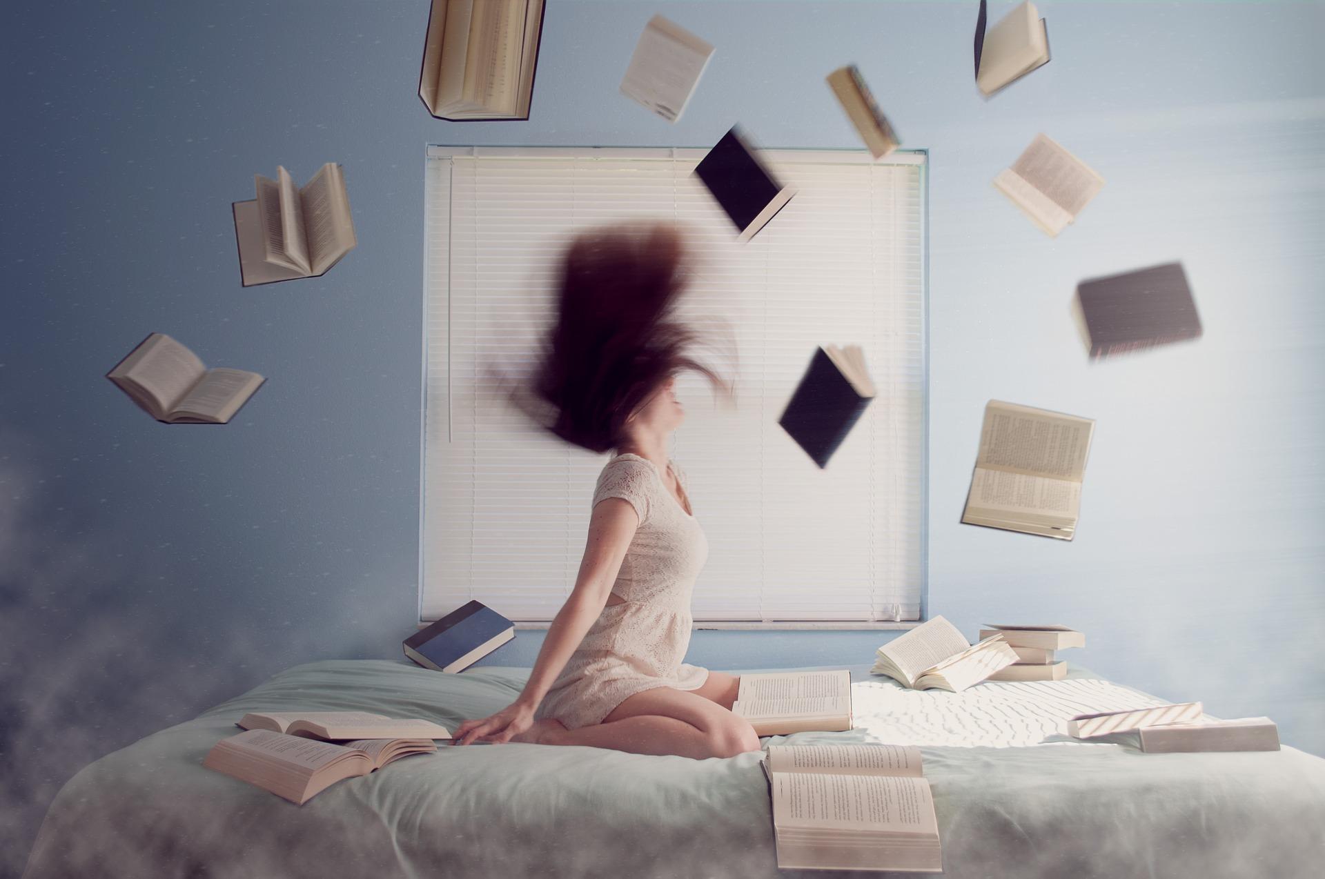 ベッドに座り本を散らばして荒ぶる女性の画像