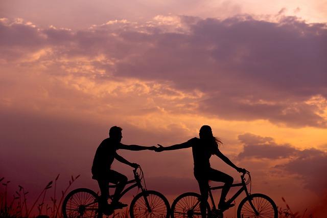 手をつなぎながらサイクリングする男女のシルエットが夕景に浮かぶ画像