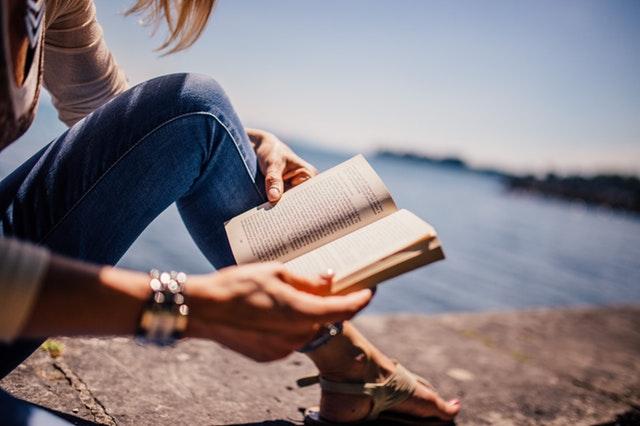 海辺で本を読む女の子の手元の画像