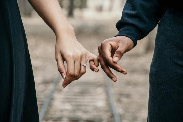 薬指に結婚指輪をして小指をつなぐ男女の画像