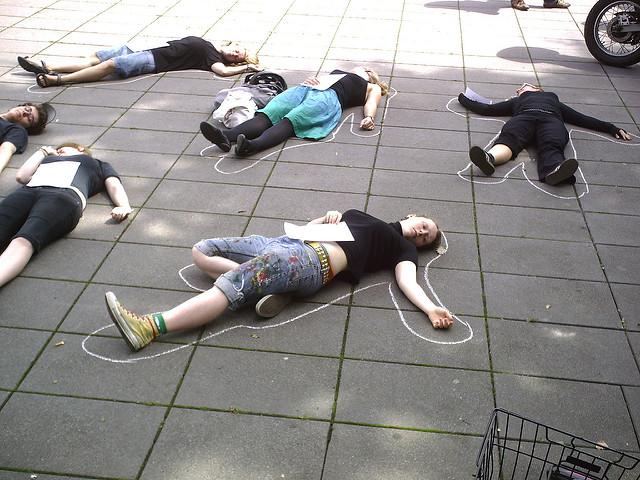 フラッシュモブで地面に横たわっている人々の画像