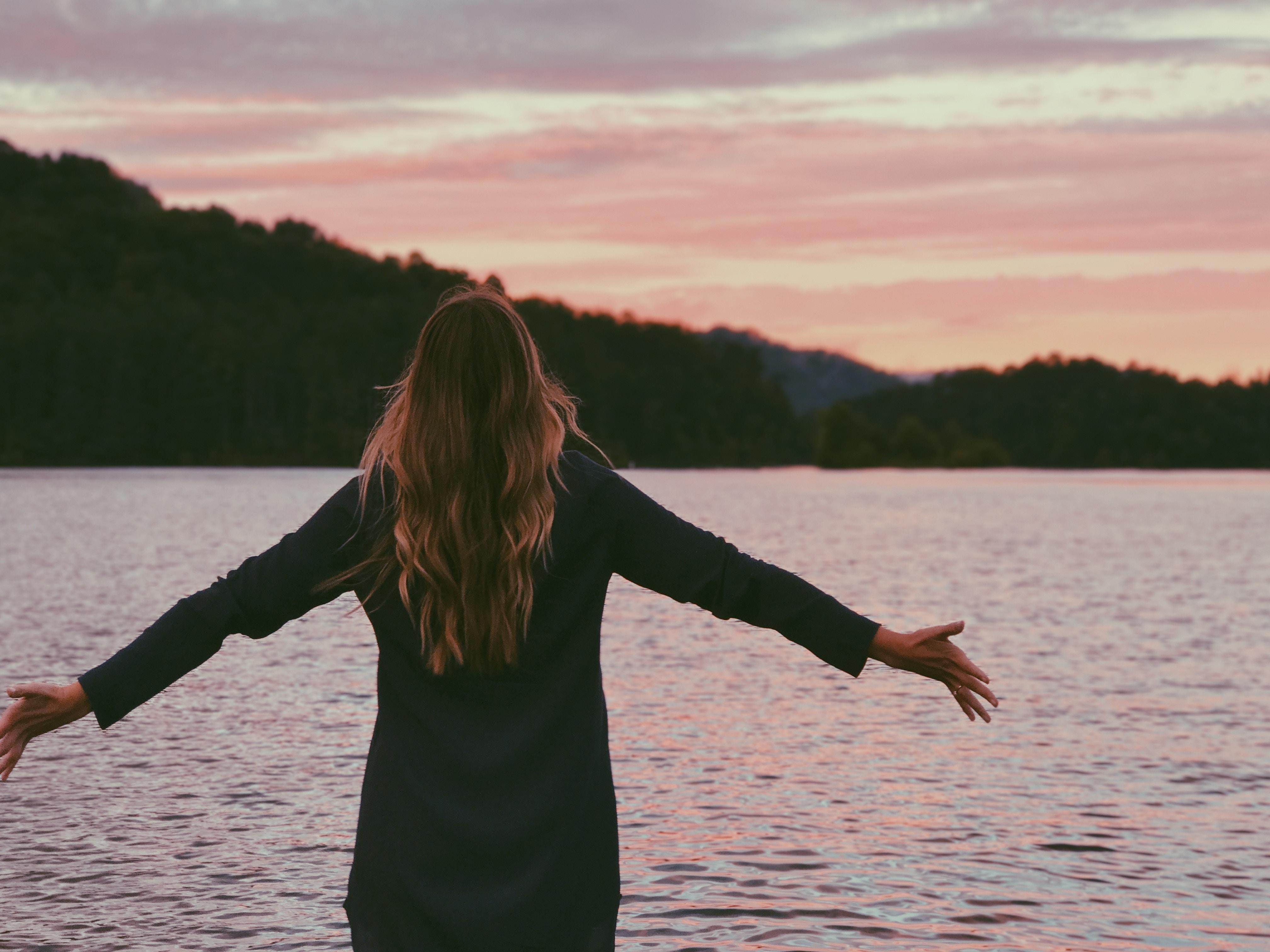 琵琶湖で気持ちよさそうに手を広げる女性の画像
