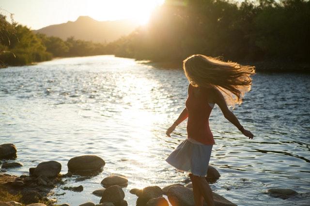 少女が岩をジャンプしながら川遊びをしている画像