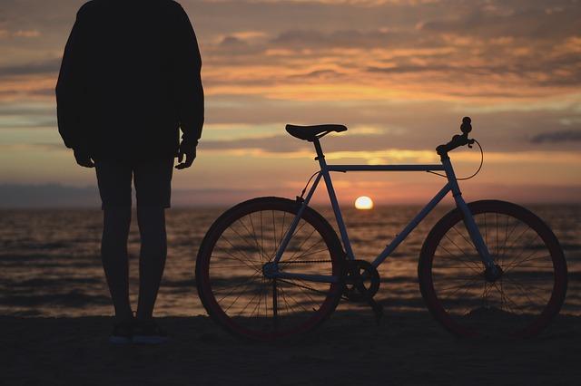 若者が自転車とともにビーチで日の出を一緒に見ている画像