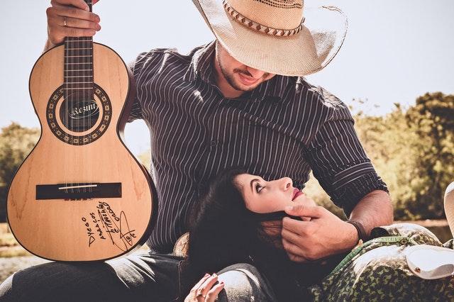 ギターを抱えて愛をささやく浮気男とその彼女の画像
