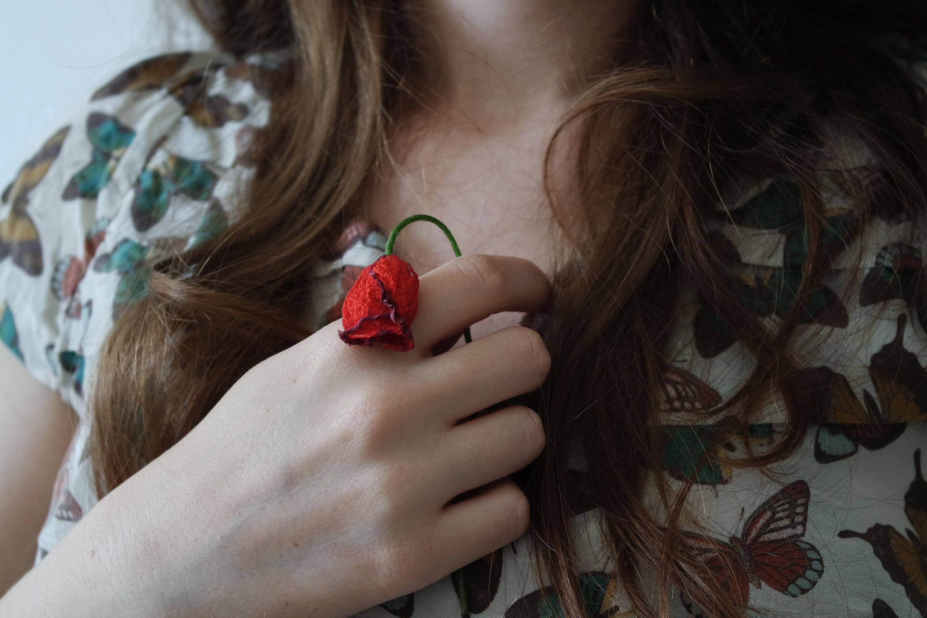 不倫になやみ咲かない花を握る女性の画像