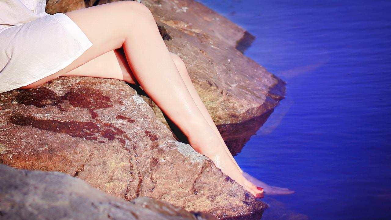女性が水に美脚を浸している画像