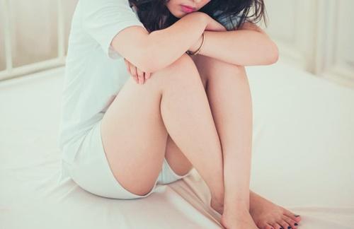 膝を抱える女性の画像