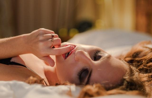 金髪の女性がベッドの上で指をくわえて快感に身悶えている画像