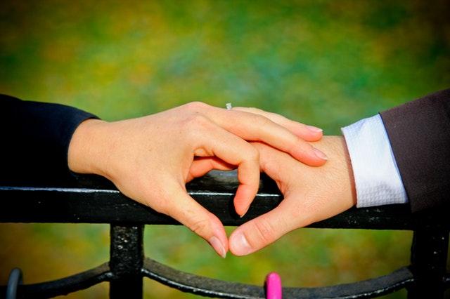 手すりの上でカップルの両手が絡み合っている画像