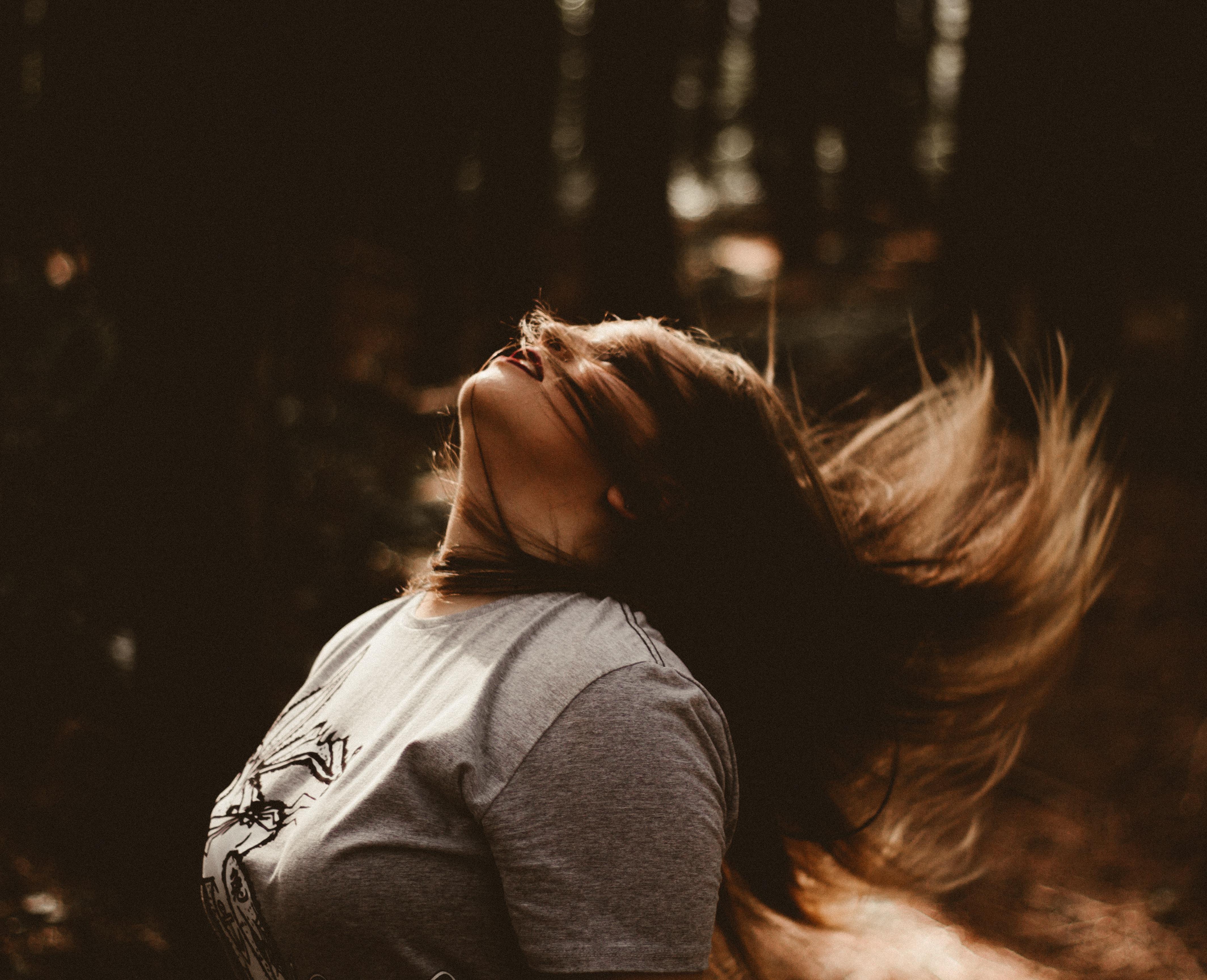 グレーのカットソーを着た髪をふりみだす女性の画像