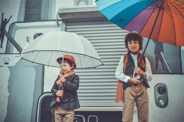 男の子が傘を持って立っている画像