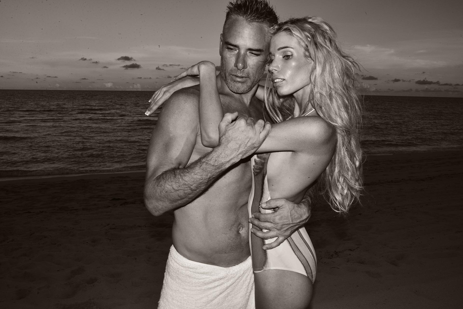浜辺で抱き合う水着の男女